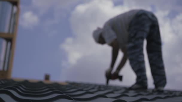 Střecha funguje. Instalatér přišroubuje kovové dlaždice ke střešní bedně. Střešní konstrukce.