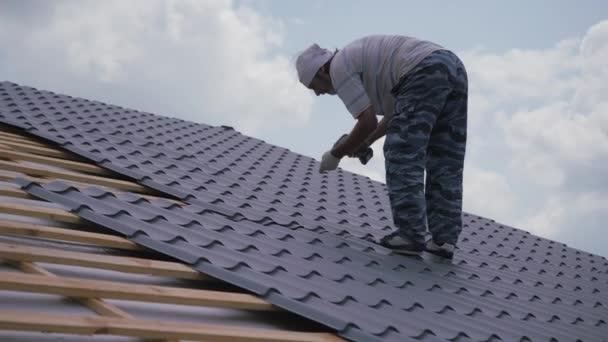 28. června 2020 - redakční - Mtsensk, Oryol region, Rusko: MAKITA power tools. Střecha funguje. Instalatér přišroubuje kovové dlaždice ke střešní bedně. Střešní konstrukce.