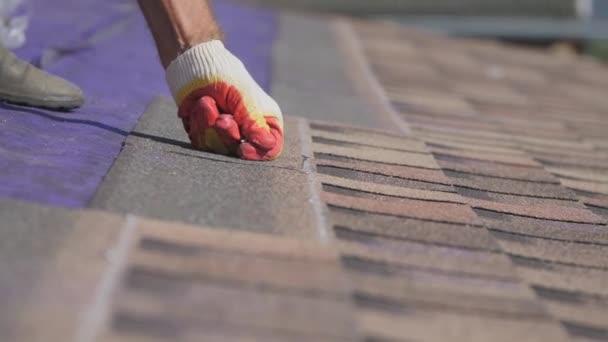 Střešní práce. Položit měkkou střechu na střechu soukromého domu. Práce s pružným střešním materiálem. Opravuje střechu hřebíkem a kladivem. Zarovnání měkkého listu dlaždic.