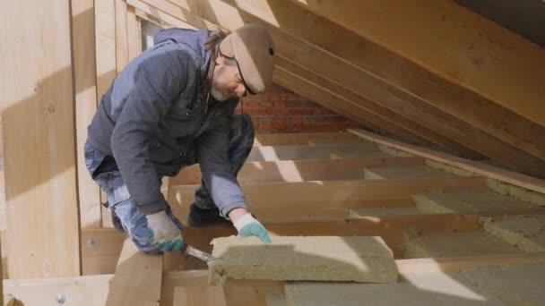 Stavební práce. Montáž izolace pomocí. Položení vícevrstvého tepelně izolačního materiálu. Izolace soukromého domu s minerální vlnou. Montáž izolace pomocí ofsetové technologie.