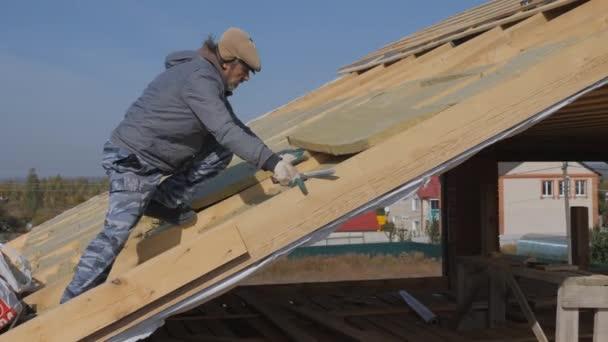 Montáž izolace pro izolaci střechy. Použití minerální vlny. Položení vícevrstvého tepelně izolačního materiálu. Izolace soukromého domu s minerální vlnou. Montáž izolace pomocí ofsetové technologie. Střešní práce.