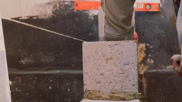 Stavební práce. Kladení tvárnic. Práce zedníků. Vyrovnání úrovně cihel se speciálním nástrojem. Ucpávání švů roztokem. Distribuce malty.