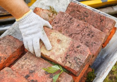 worker puing the brick in the wheelbarrow outdoor. hand closeup