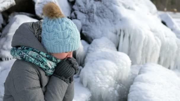 zmrazené žena zahřeje na zasněžené skalnaté pobřeží