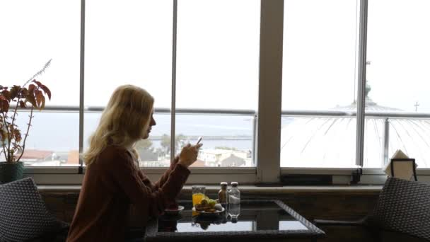 woman with smartphone sits at breakfast in hotel overlooking the city