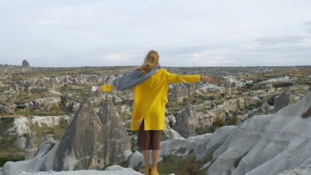 Žena stojící zpět kochat výhledem na skalnaté údolí Kappadokie