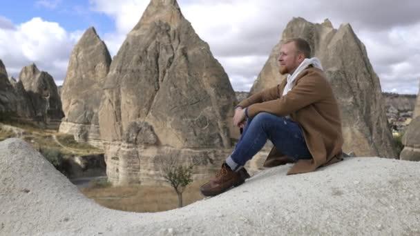 man sitting among the rocks of cappadocia