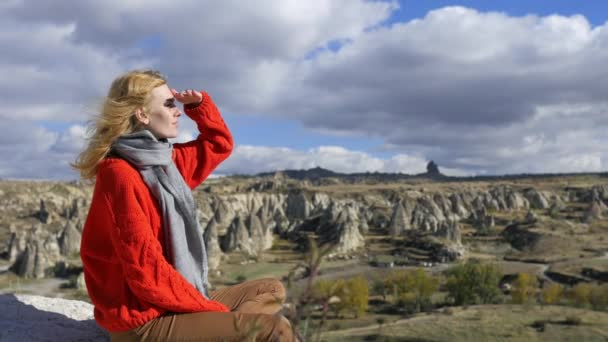 woman sits on a cliff of a rocky valley and looks into the distance