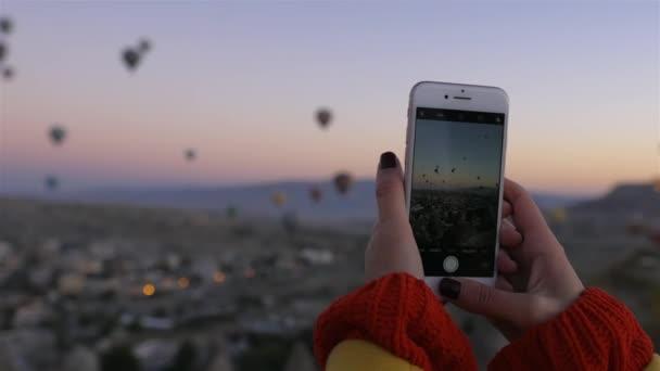 Frau schießt mit Handy auf Luftballon in Kappadokien