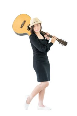 Woman carrying acoustic guitar on shoulder