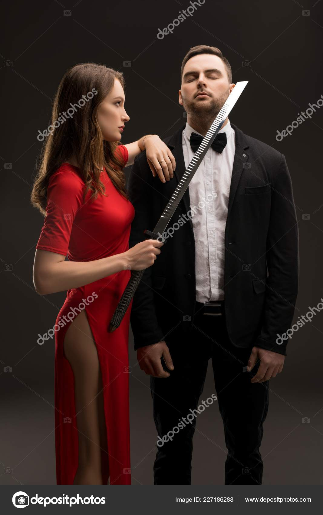 daef6c1dc4ef Beautiful girl in the evening red dress with deep cut holding a sword and  handsome man wearing white shirt, bow tie and costume full-length shot —  Photo by ...