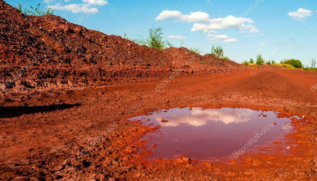 Dry red soil with puddle in Kryvyi Rih, Ukraine