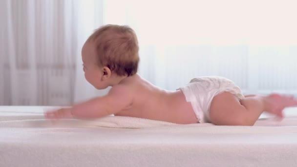 Joyful little baby lies on belly