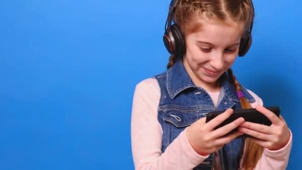 Fiatal csinos lány a fejhallgató játék a videó-játék lány smartphone