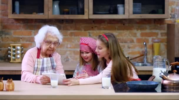 Granddaughter and grandmother with tablet at kitchen