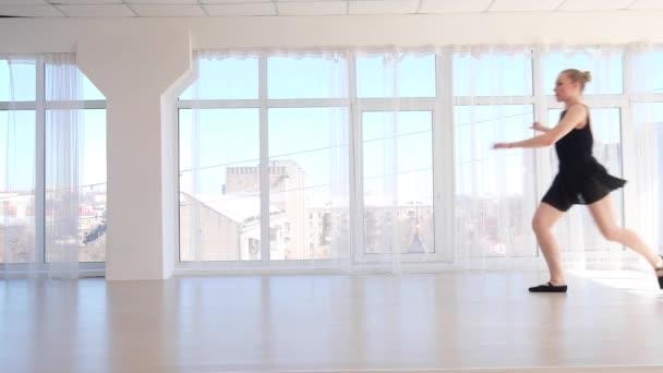 Ballerina dancer performing a jump in white studio