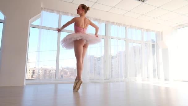 attraktive Balletttänzerin in rosa Tutu übt und lächelt