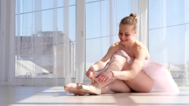 Young ballerina in tutu sitting on the floor and tying pointe shoes
