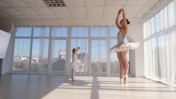 junge hinreißende Ballerina lehrt kleine Tochter tanzen im Studio