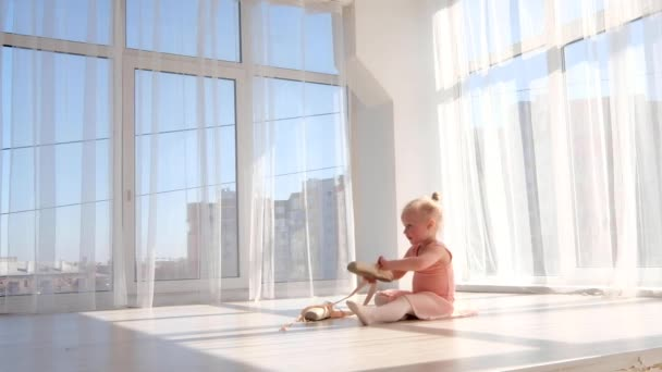 Beautiful young ballet dancer in tutu sitting on the floor in white light room and tying pointe shoes. Choreography and ballet concept