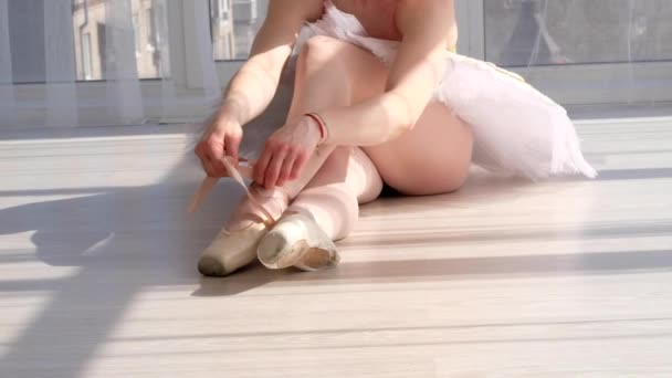 Graceful young ballet dancer in tutu sitting on the floor in white light room and tying pointe shoes. Choreography and ballet concept