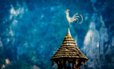 View of metal rooster on the little wooden tower roof