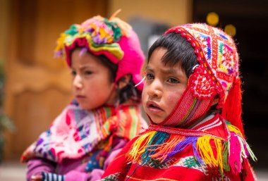 Peru, Cusco - 13 October 2018: Little girls in colorful national clothing looking ,on the blurred background, in Cusco stock vector