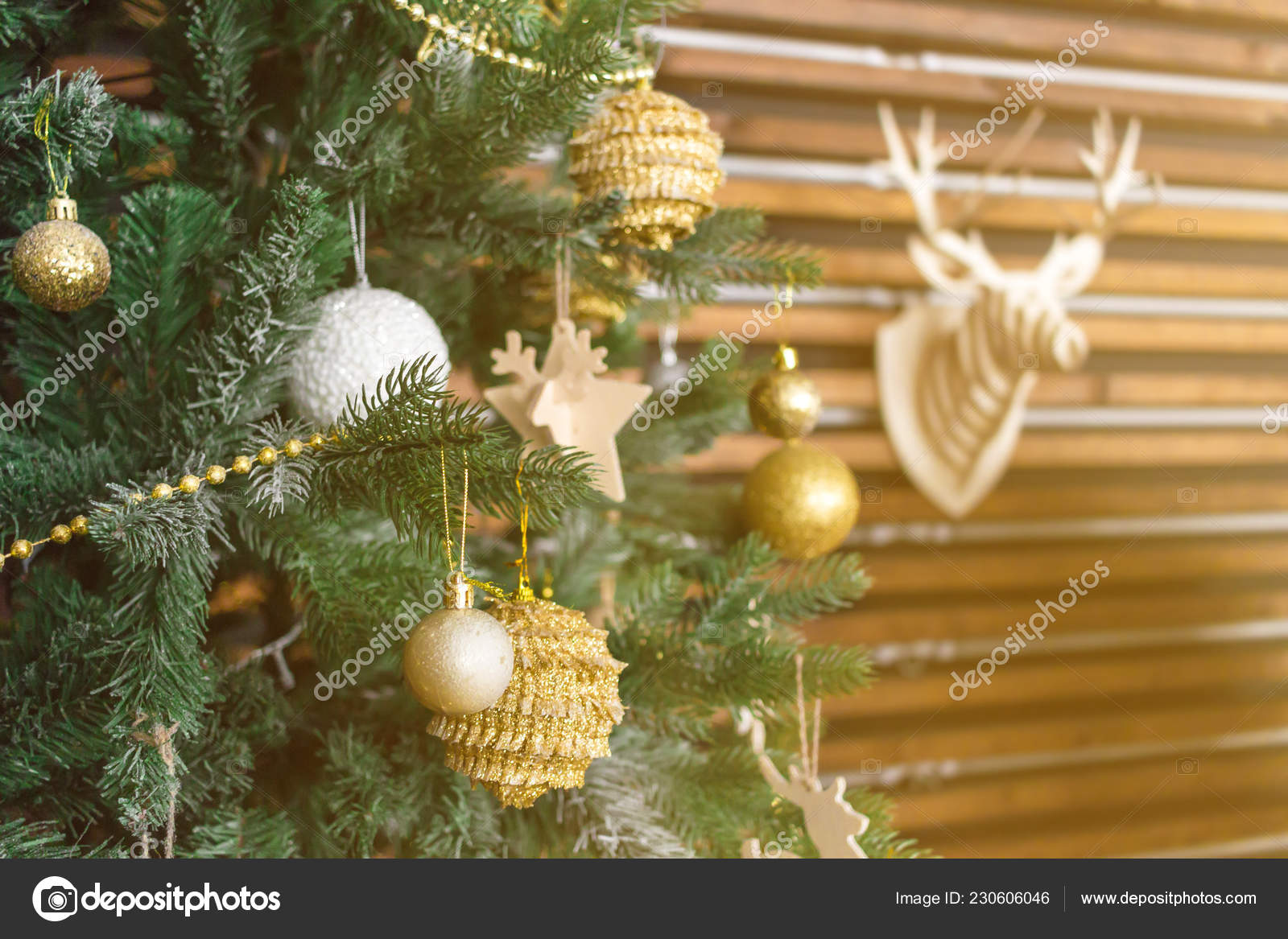 Christmas Tree With Golden Balls Star Other Decorations Deer Head Model On The Wall As Background New Year Theme Concept Sun Shining Orange Toned Stock Photo C Axivan 230606046