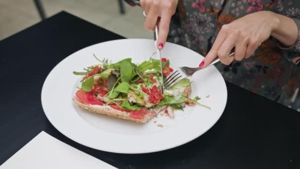 Sendvič na bílé desce jedí s nožem a vidličkou