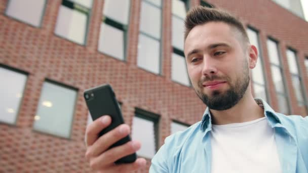 Man with Beard Using a Phone against a Brick Building