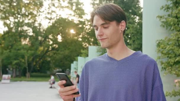 Mladý muž s použitím telefonu ve městě