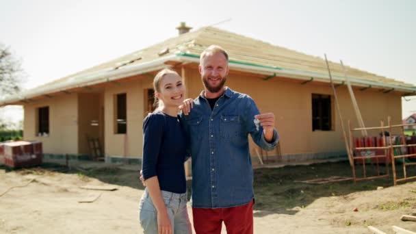 Dva mladí lidé stojící venku na staveništi před jejich nový dům. Střední zásah. Měkké zaostření