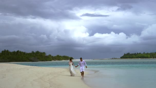 Newlyweds hold hands and are running on a gorgeous white sand beach and turquoise water.