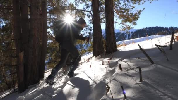 Guy climbs uphill on snowshoes in winter