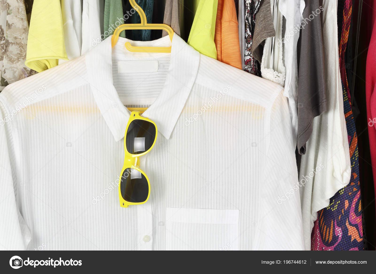 Λευκή Μπλούζα Γυαλιά Ηλίου Κρεμάστρα Μπροστά Από Άλλα Γυναικεία Ρούχα —  Φωτογραφία Αρχείου cfdfdd0bbed