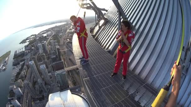 Toronto, Ontario, Canada-September 9, 2017: Two young people doing the Edgewalk in the CN Tower. The CN tower is a Canadian symbol considered to be one of the marvels of the modern world. The Edgewalk is a major attraction in the city
