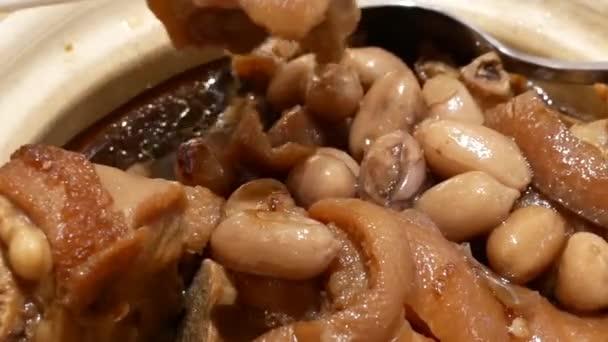 Bewegung der Leute essen geschmortes Schweinefleisch und Erdnüssen auf Tisch im China-restaurant
