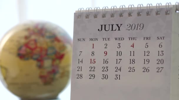 Motion of July 2019 calendar with blur earth globe turning background