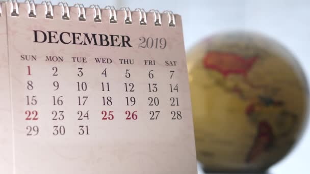 Motion of December 2019 calendar with blur earth globe turning background