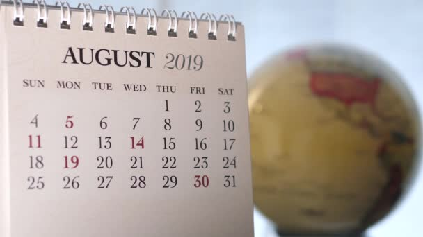 Motion of August 2019 calendar with blur earth globe turning background