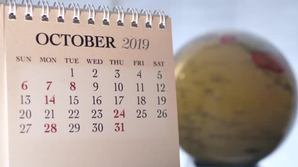 Motion of October 2019 calendar with blur earth globe turning background