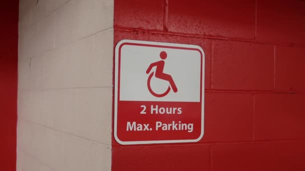 Motion of red two hours maximum parking sign on wall