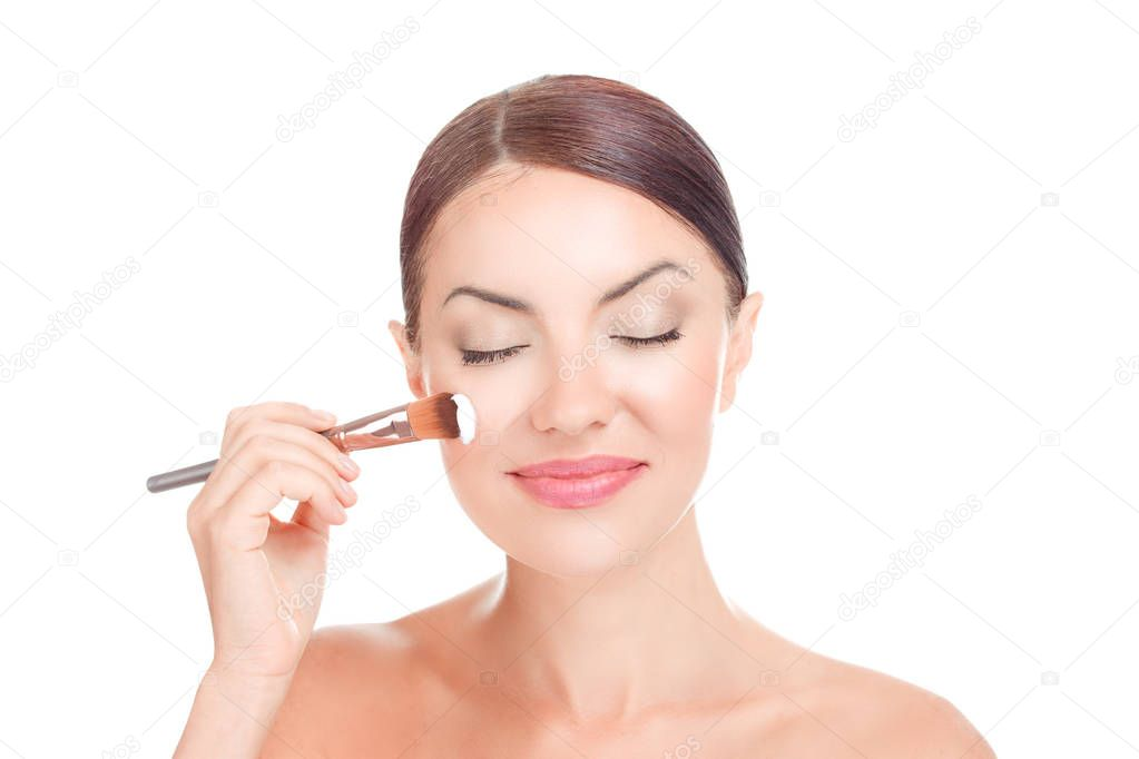 Beautiful teenage girl applying cosmetic cream creamy mask on her face with tassel brush skin care concept attractive brunette girl on white background. Mixed race african american caucasian brazilian