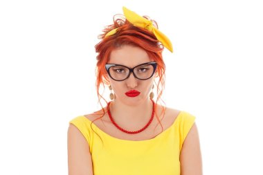 Portrait of an upset sad young casual girl standing with arms down. Caucasian person in vintage yellow dress and coral necklace with red lipstick, redhead hair isolated on white studio background.