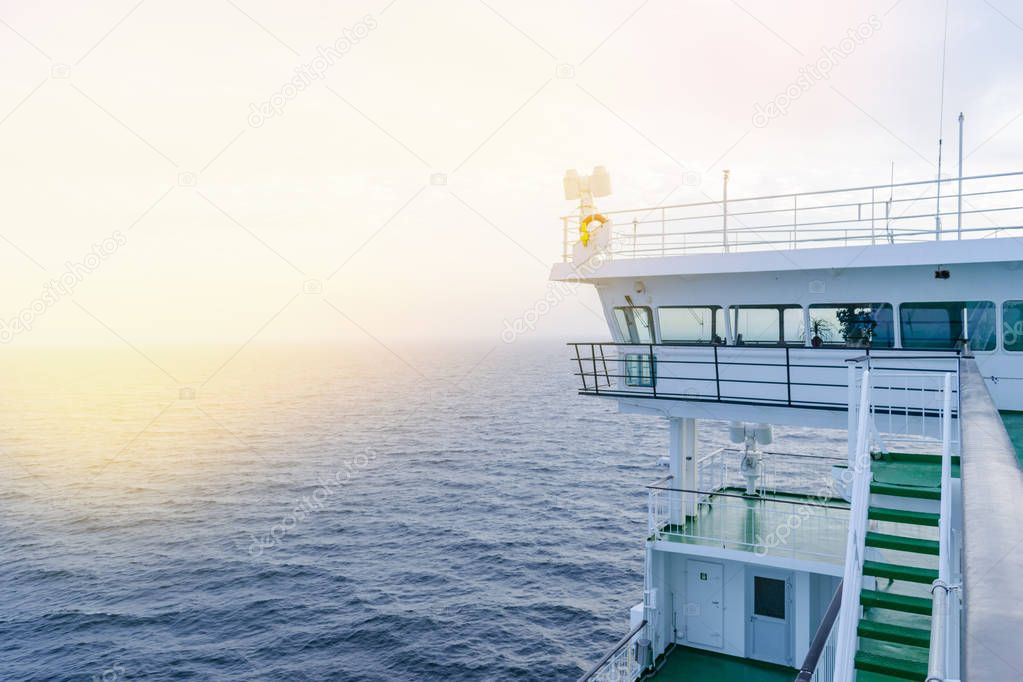 Cruise ship white cabin with big windows. Wing of running bridge of cruise liner. White cruise ship on a blue sky with radar and navigation system. Captain's cabin. Ocean sunset background.