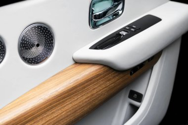 Door handle with power window control buttons of a luxury passenger car. White perforated leather interior with stitching and natural wood panel. Modern car interior details. Car detailing. Car inside