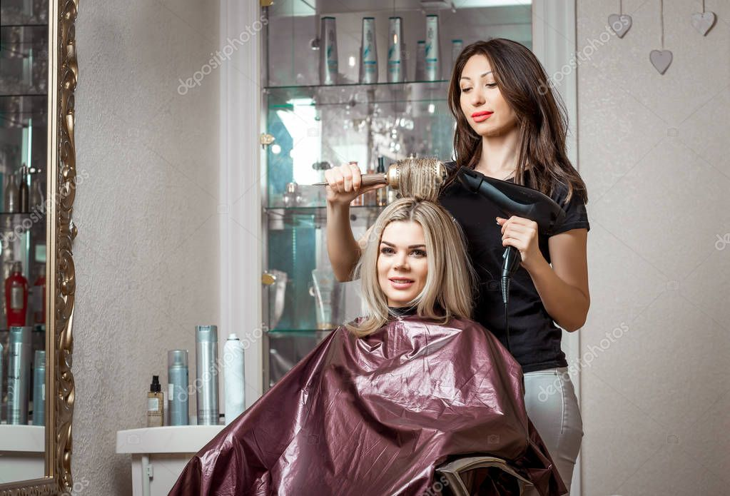 Stylish professional, hairdresser doing hairdoing to the client with a hair dryer on the background of the hairdressers salon