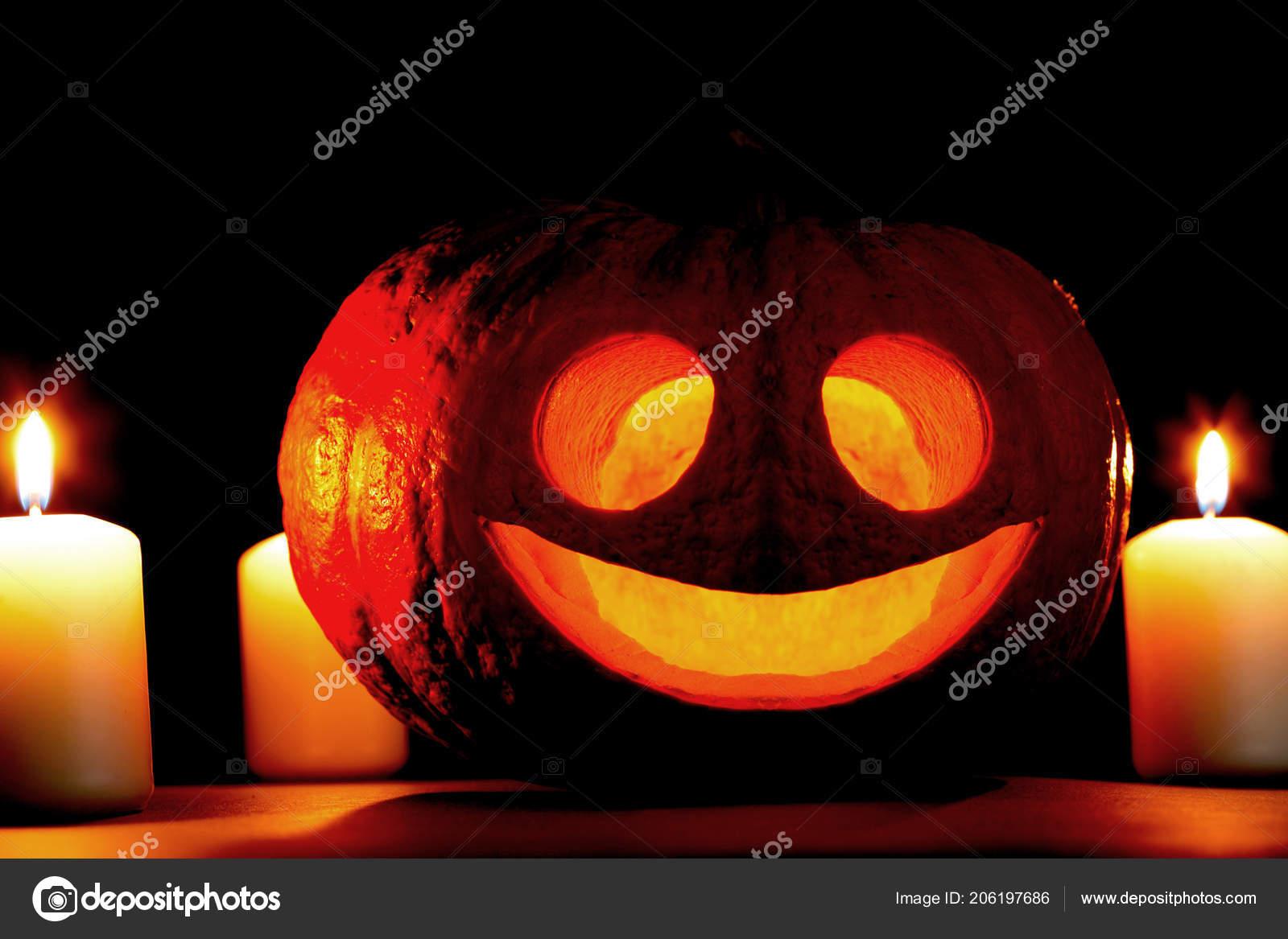 funny halloween pumpkin burning candles black background stock