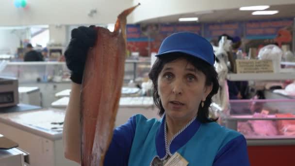 Město Petropavlovsk, Friesdorf, Rusko - 20. května 2018: prodavačka ukazuje uzené solené červený losos na rybím trhu k zajištění kvality a dobroty ekologicky šetrné volně žijícího lososa Kamčatka vyrábí ochranné známky Kamčatka Neptun