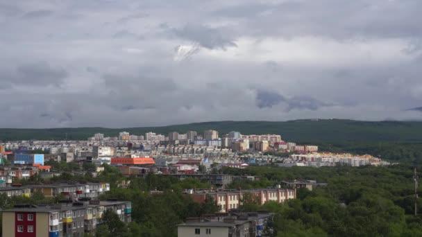 Letní pohled naprosto poloostrova Kamčatka: rozvoj měst města Petropavlovsk-Kamchatsky na pozadí sopky, mraky, plovoucích po obloze, kolem hory. Ruský Dálný východ. Časová prodleva